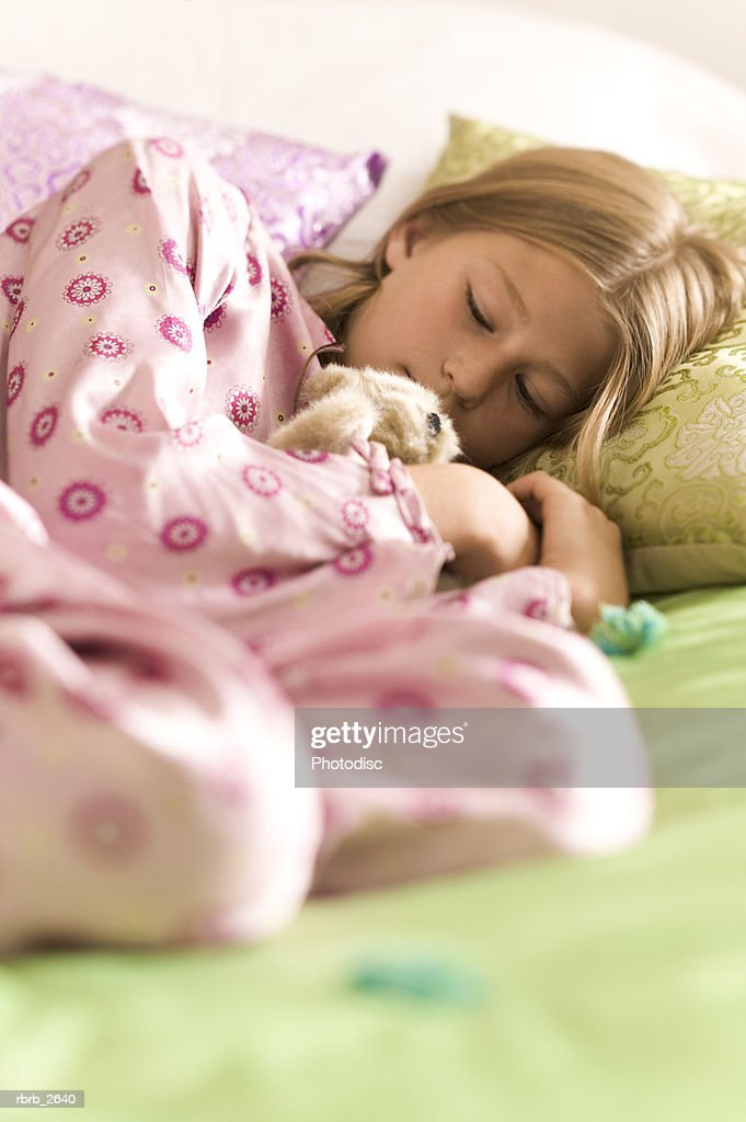 teenage lifestyle shot of a girl in pink pajamas as she sleeps on her bed : Foto de stock