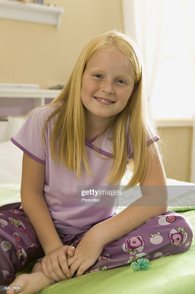 teenage lifestyle shot of a girl in purple pajamas as she sits on her bed and smiles : Foto de stock