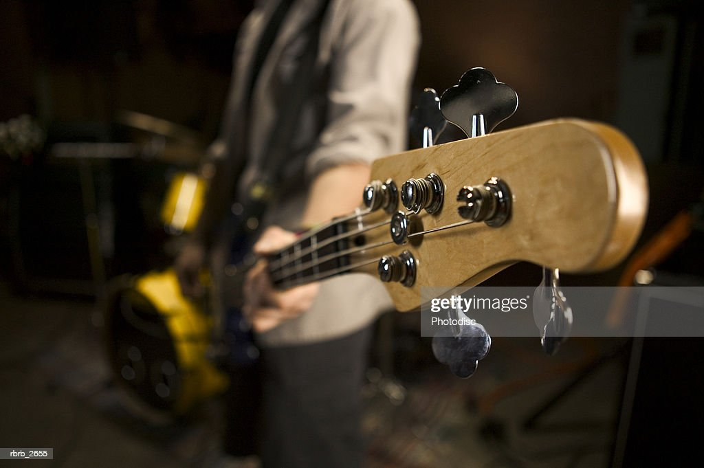 teenage lifestyle shot of a male guitar player as he practices with his rock band : Foto de stock