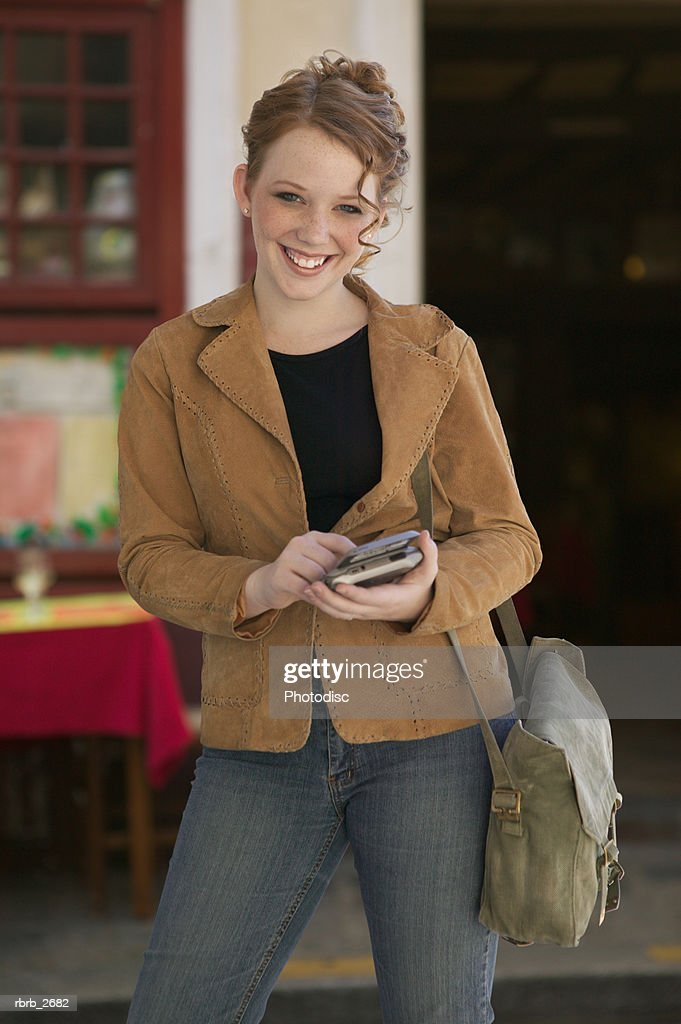 teenage lifestyle shot of a redheaded female in a brown jacket as she stands using an electronic planner : Foto de stock