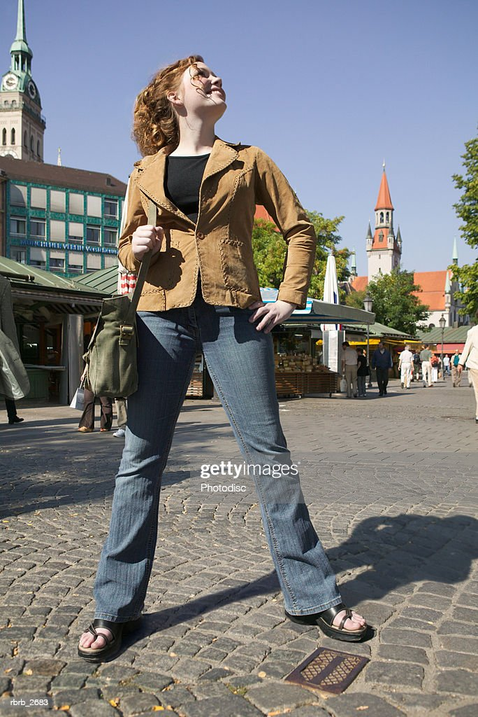 teenage lifestyle shot of a redheaded female in a brown jacket as she stands in a european plaza : Foto de stock