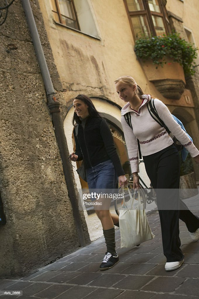 teenage lifestyle shot of a two female friends as they walk down a european street : Stockfoto