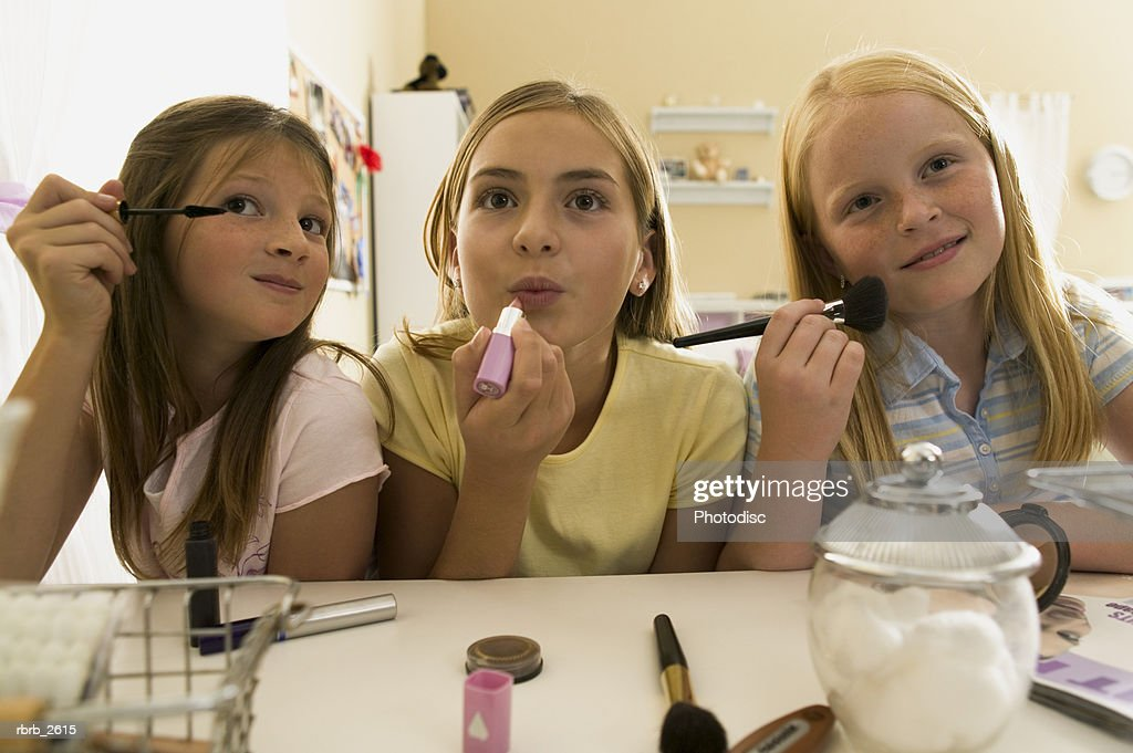 teenage lifestyle shot of three female friends as they sit at a mirror putting on make up : Foto de stock