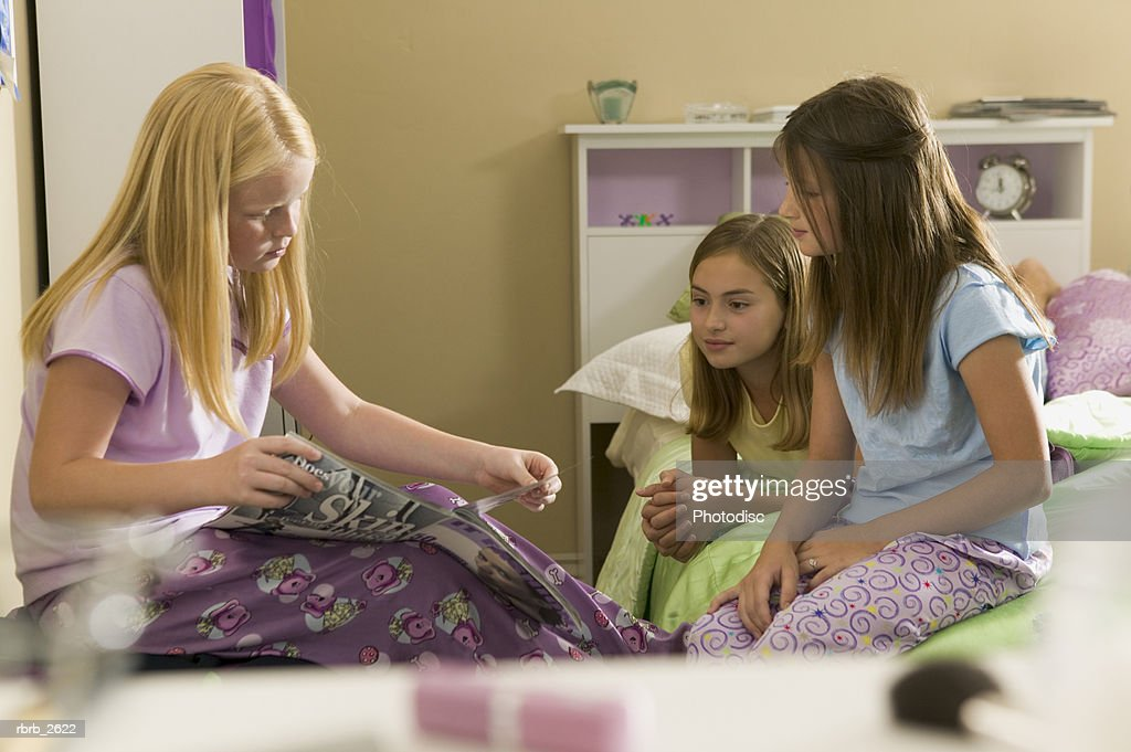 teenage lifestyle shot of three female friends as they sit in a bedroom reading magazines : Foto de stock