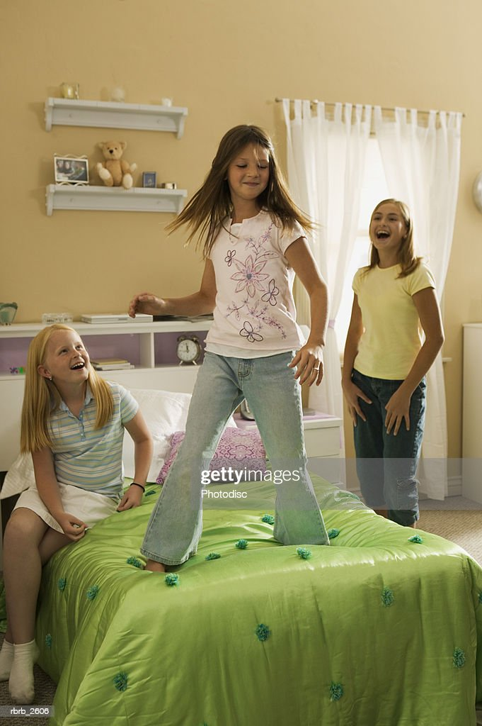 teenage lifestyle shot of three girls as they play together in a bedroom : Stockfoto