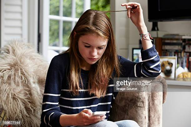 teenage looking at cellphone and playing with her hair - teenage girls stock pictures, royalty-free photos & images