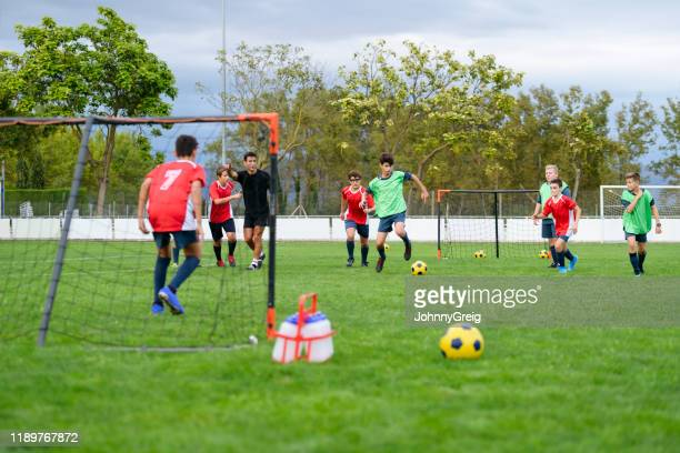 teenage male footballer dribbling ball toward goal - soccer competition stock pictures, royalty-free photos & images