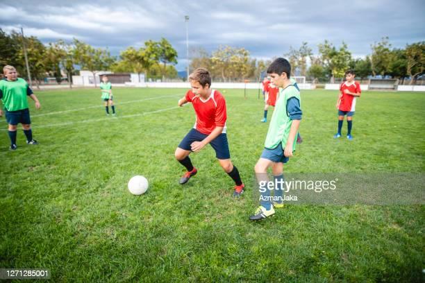 teenage male footballer dribbling vergangenheit verteidiger in der praxis - jugendmannschaft stock-fotos und bilder