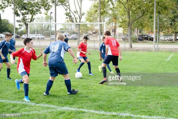 mannelijke tiener voetballers die in de oefenwedstrijd concurreren - match sport stockfoto's en -beelden