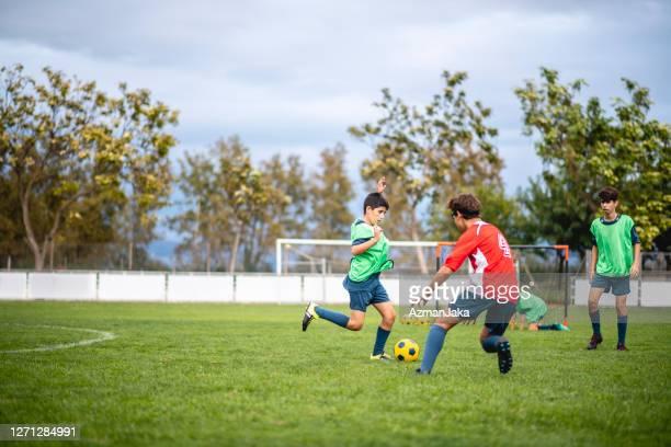 10代の男性サッカー選手ドリブルと練習での守備 - ドリブル ストックフォトと画像