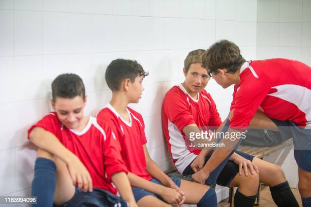 teenage male footballers getting ready in locker room - young boys changing in locker room stock pictures, royalty-free photos & images