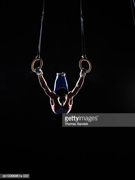 teenage (16-17) male gymnast practicing on rings against black background - gymnastics stock pictures, royalty-free photos & images