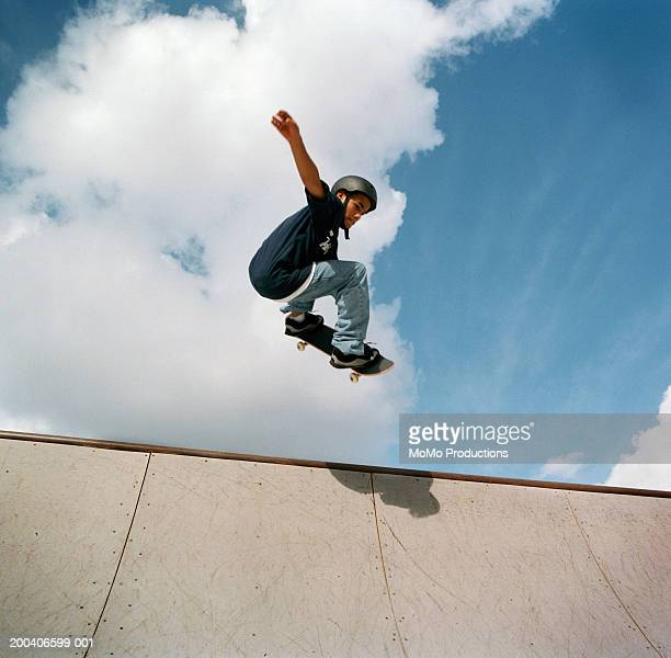 Teenage male (14-16) skateboarder jumping on halfpipe, low angle view