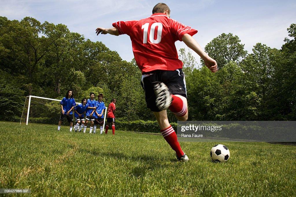Teenage male (18-20) soccer player free kicking against opposing team : Stock Photo
