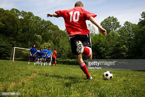 Teenage male (18-20) soccer player free kicking against opposing team