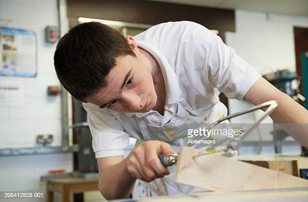 Teenage male student (13-15) sawing plank in woodwork class