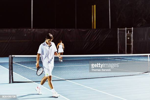 Teenage male tennis player walking onto outdoor court to practice with teammate at night
