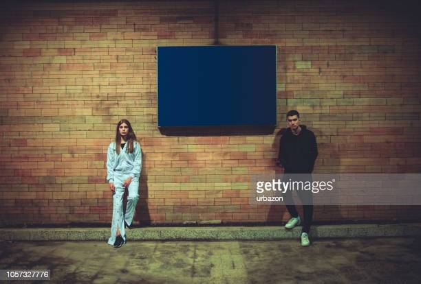 teenage man and a girl leaning on wall - side by side stock pictures, royalty-free photos & images