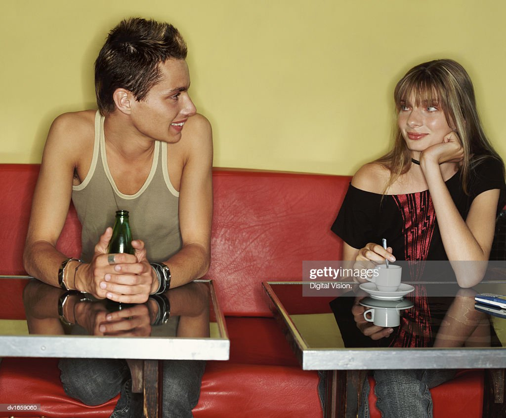 Teenage Man and Woman Sitting Side by Side in a Cafe and Flirting : ストックフォト