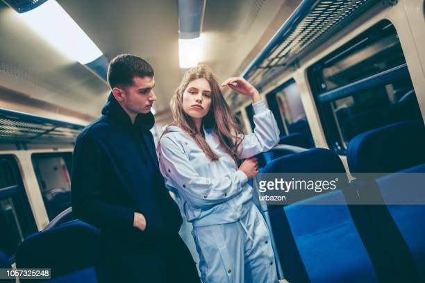 Teenage man and woman standing in train