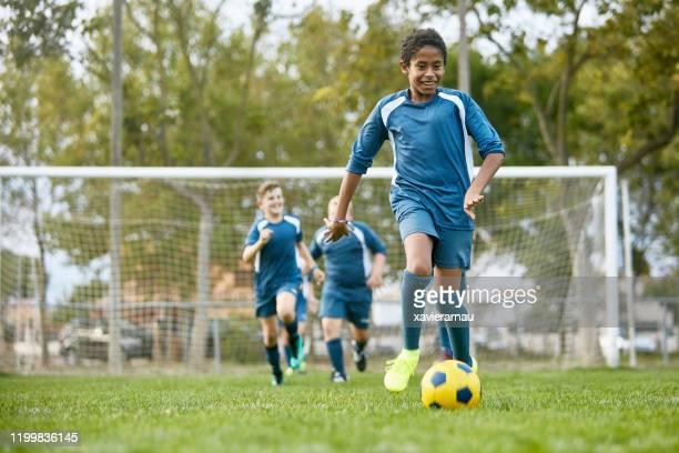 jogador de futebol mestiço adolescente que dribla longe dos teammates - sporting term - fotografias e filmes do acervo