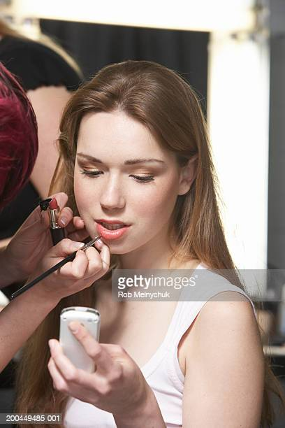 Teenage model (16-18) using cell phone while being styled backstage