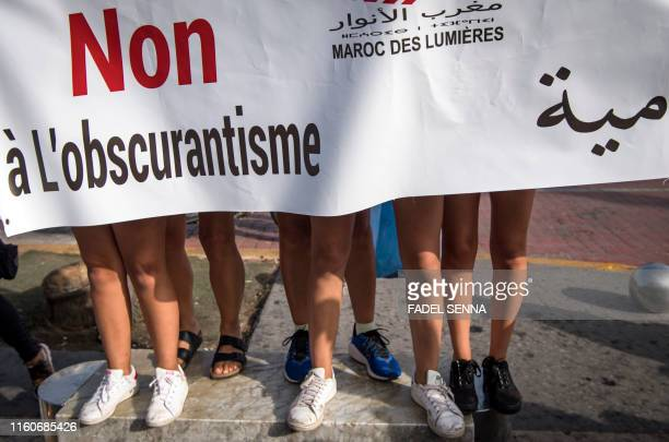 TOPSHOT Teenage Moroccan girls stand behind a large banner reading in Arabic and French no to obscurantism during a demonstration in Casablanca on...