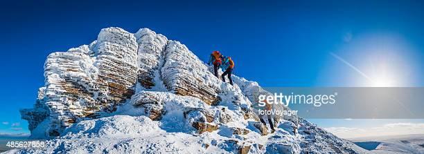Teenage mountaineer climbing snowy summit multiple exposure panorama winter sunburst