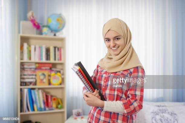 Teenage muslim student girl standing at home