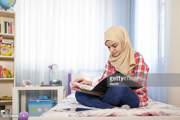 Teenage muslim student girl studying at home