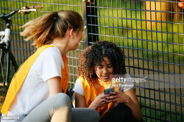 teenage netball player looking at her mobile phone on outdoor netball court