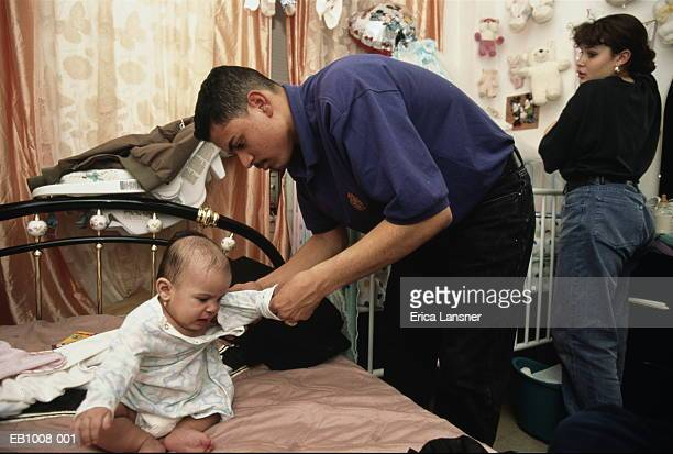 teenage parents (15-18) in bedroom, father dressing baby (6-9 months) - bent over babes stock pictures, royalty-free photos & images