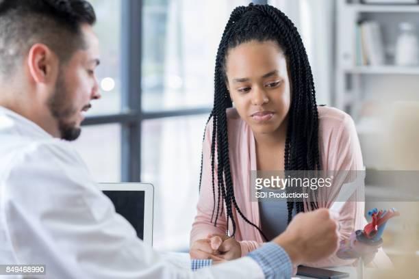 Tiener patiënt bespreekt behandelplan met cardioloog