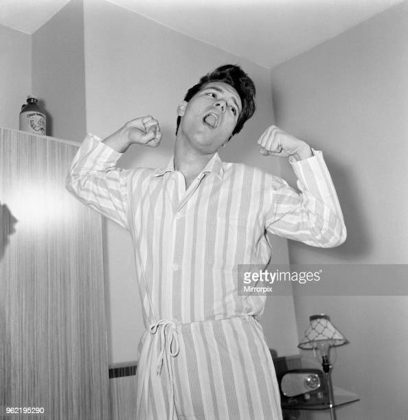 Teenage pop idol Cliff Richard relaxes on his divan at his Winchmore Hill home. His is wearing flannelette striped pyjamas, 22nd November 1960.