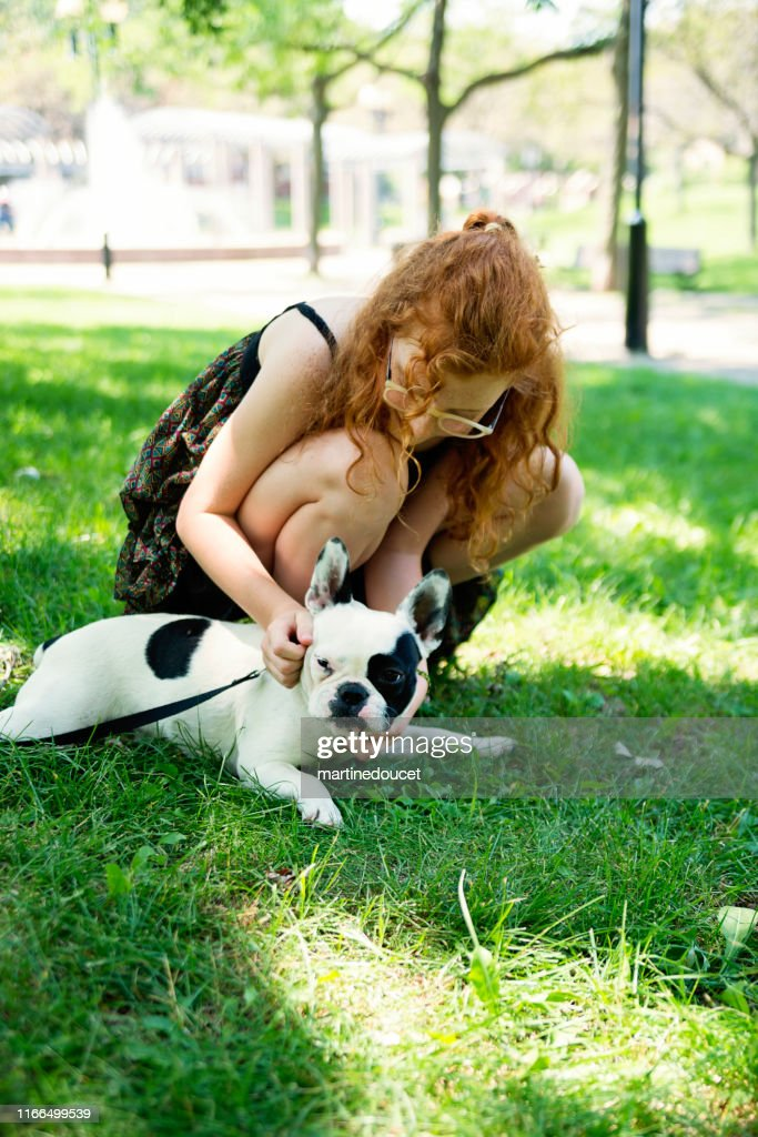 Teenage redhead girl in a park with a dog : Stock Photo