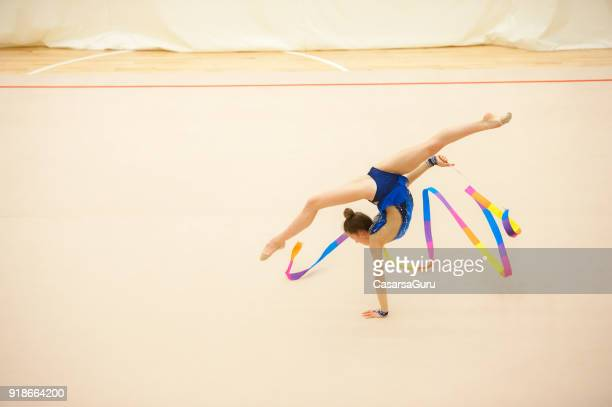 teenage rhythmic gymnastics athlete doing ribbon routine - rhythmic gymnastics stock pictures, royalty-free photos & images