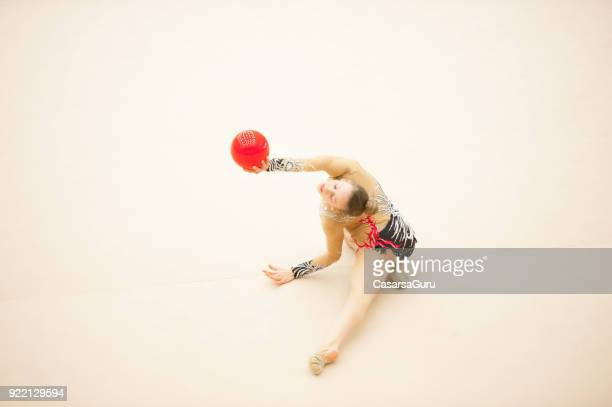 teenage rhythmic gymnastics athlete practicing with ball - rhythmic gymnastics stock pictures, royalty-free photos & images
