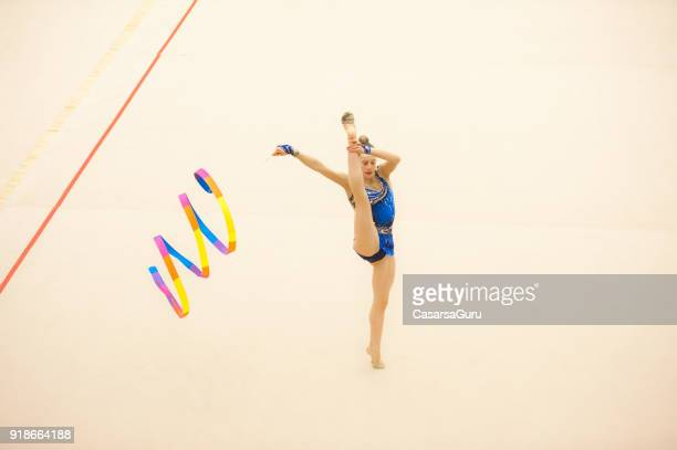 teenage rhythmic gymnastics athlete practicing with ribbon - rhythmic gymnastics stock pictures, royalty-free photos & images