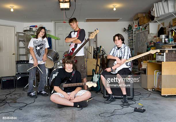 Teenage rock band posing in garage