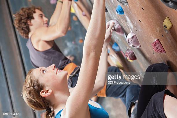 Teenage Rock Climbers looking up while climbing in Indoor Gym