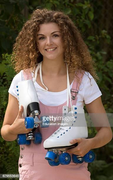 Teenage roller skater carrying her quad skates