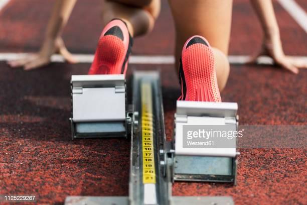 teenage runner kneeling on starting block, close up - teenage girls feet stock-fotos und bilder