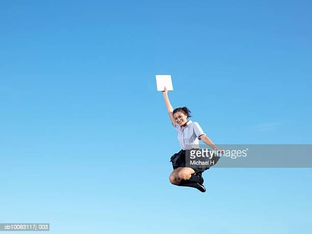 Teenage school girl (16-18) jumping in blue sky, smiling