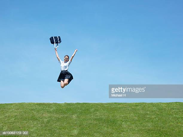 Teenage schoolgirl (16-17) jumping against clear sky, low angle view