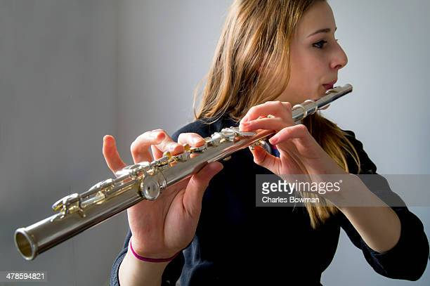Teenage schoolgirl practises playing her flute