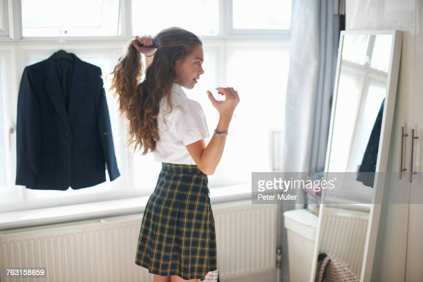 Teenage schoolgirl styling back long hair in bedroom