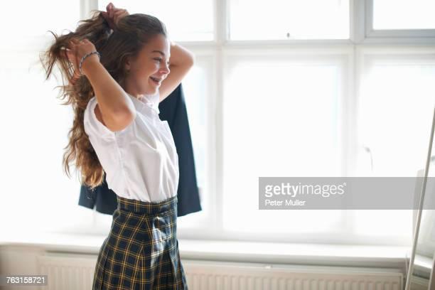 teenage schoolgirl styling long hair in bedroom - écolière photos et images de collection