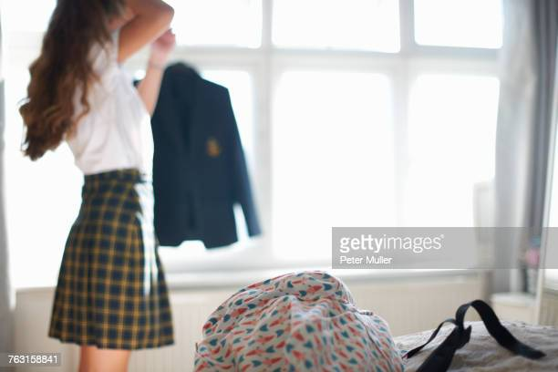 Teenage schoolgirl styling long hair in bedroom