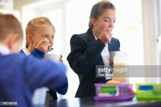 Teenage schoolgirl with sister and brother eating breakfast cereal in kitchen