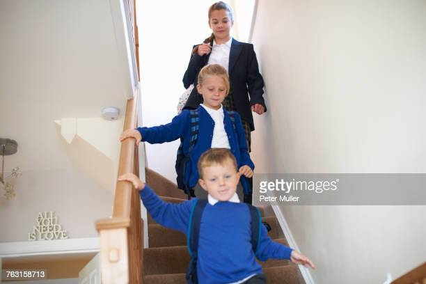 Teenage schoolgirl with sister and brother in uniforms moving downstairs